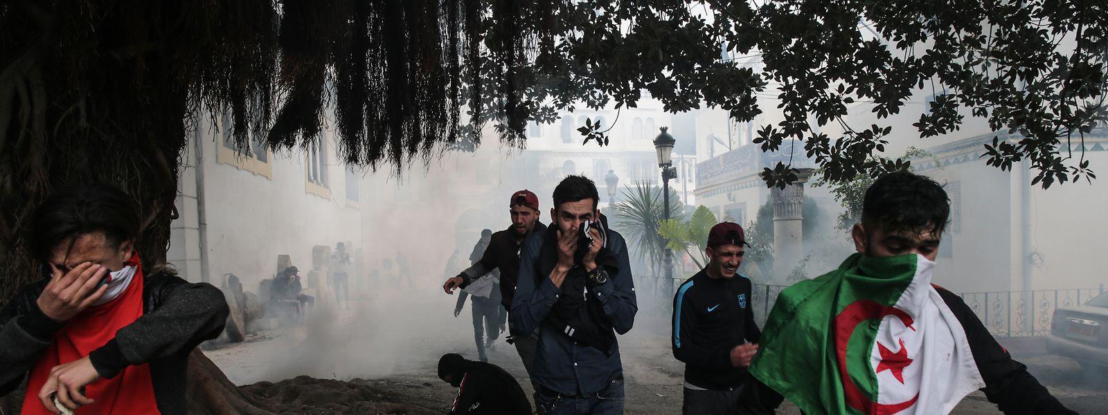 Demonstranten, die gegen den algerischen Präsidenten Abdelaziz Bouteflika demonstrieren, bedecken ihre Gesichter zum Schutz vor Tränengas.