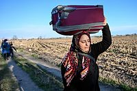 TOPSHOT - A migrant carries her belongings walking towards greece border on February 28 , 2020 near Turkey-Greece border near Pazarkule border gate in Edirne. - Turkey will no longer close its border gates to refugees who want to go to Europe , a senior official told AFP on February 28, shortly after the killing of 33 Turkish soldiers in an airstrike in northern Syria. (Photo by Ozan KOSE / AFP)