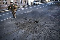 TOPSHOT - A security forces officer passes by a hole on a road made by overnight shellings in Stepanakert during fighting over the breakaway region of Nagorno-Karabakh on October 17, 2020. - Azerbaijan's President Ilham Aliyev vowed on October 17, 2020 to take revenge on Armenia after a missile strike killed 12 sleeping people in the city of Ganja, a dramatic escalation in the conflict over the disputed Nagorno-Karabakh region. (Photo by ARIS MESSINIS / AFP)