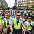 CORRECTION - Police escort far-right demonstrators led by 'Unite the Right' organizer Jason Kessler (holding flag) during a rally at Lafayette Park opposite the White House August 12, 2018 in Washington, DC, one year after the deadly violence at a similar protest in Charlottesville, Virginia. - Last year's protests in Charlottesville, Virginia, that left one person dead and dozens injured, saw hundreds of neo-Nazi sympathizers, accompanied by rifle-carrying men, yelling white nationalist slogans and wielding flaming torches in scenes eerily reminiscent of racist rallies held in America's South before the Civil Rights movement. (Photo by Nicholas Kamm / AFP) / CORRECTION: �The erroneous mention[s] appearing in the metadata of this photo by Nicholas Kamm has been modified in AFP systems in the following manner: ['Unite the Right' organizer Jason Kessler] instead of  [demonstrators]. Please immediately remove the erroneous mention[s] from all your online services and delete it (them) from your servers. If you have been authorized by AFP to distribute it (them) to third parties, please ensure that the same actions are carried out by them. Failure to promptly comply with these instructions will entail liability on your part for any continued or post notification usage. Therefore we thank you very much for all your attention and prompt action. We are sorry for the inconvenience this notification may cause and remain at your disposal for any further information you may require.�