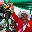 """(FILES) In this file photo taken on December 15, 2017 Zimbabwe's President Emmerson Mnangagwa lifts the hand of Oppah Muchinguri Kashiri whom he appointed the ZANU-PF party's first woman chairperson during the ZANU-PF  extraordinary congress in Harare. One of Zimbabwe's two vice presidents was injured during an explosion at a ruling ZANU-PF election rally which President Emmerson Mnangagwa survived in the second city of Bulawayo, state television said on June 23, 2018. """"In news just received Vice President Kembo Mohadi, Oppah Muchinguri-Kashiri the ZANU PF chairperson and political commissar Engelbert Rugeje were  injured in the explosion,"""" Zimbabwe Broadcasting Corporation (ZBC) said.  / AFP PHOTO / Jekesai NJIKIZANA"""