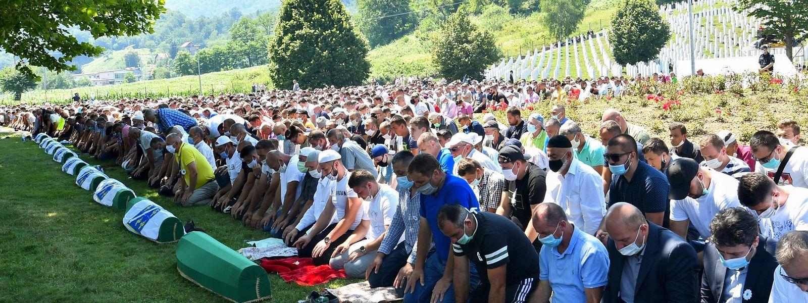 Bosnisch-muslimische Männer, die Gesichtsmasken tragen, beten während einer Bestattungszeremonie zum 25. Jahrestag des Massakers von Srebrenica auf dem Potocari-Gedenkfriedhof, einem Dorf außerhalb von Srebrenica.