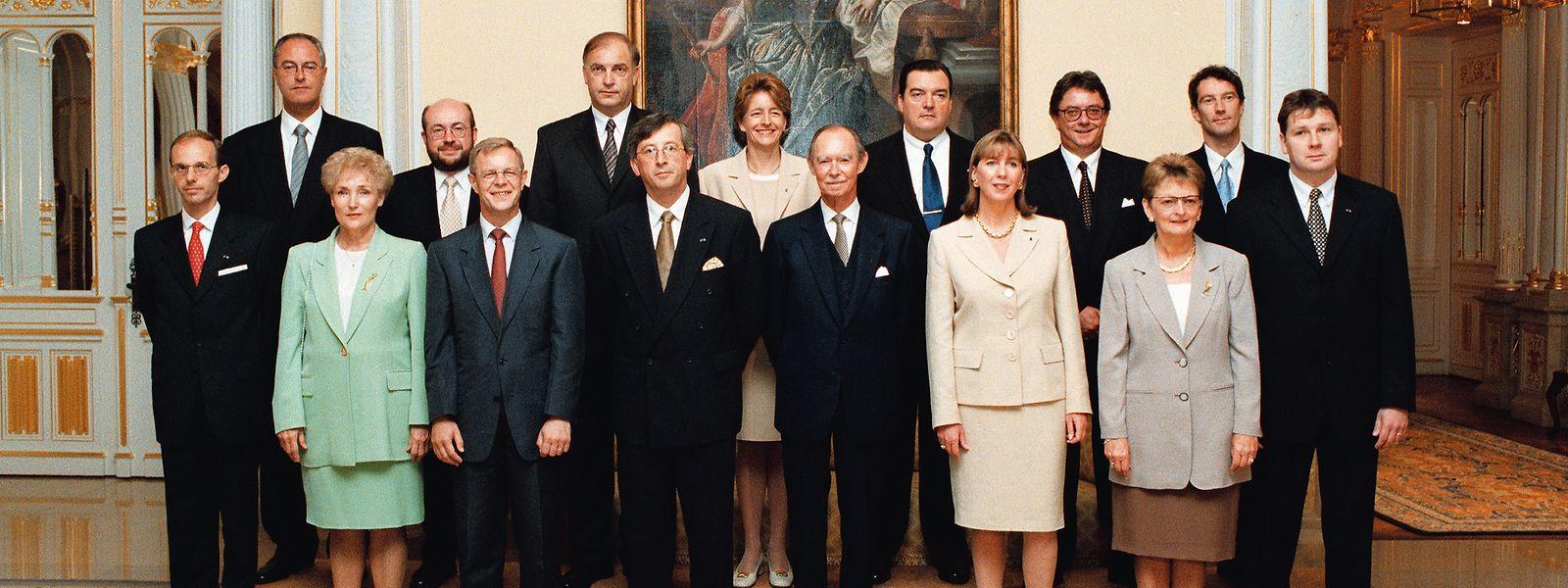 Die CSV-DP-Regierung nach ihrer Vereidigung am 9. August 1999: V.l.n.r. 1. R.: Luc Frieden, Erna Hennicot-Schoepges, Fernand Boden, Jean-Claude Juncker, Großherzog Jean, Lydie Polfer, Marie-Josée Jacobs, Michel Wolter: 2. R.: Jos Schaack, François Biltgen, Charles Goerens, Anne Brasseur, Henri Grethen, Carlo Wagner, Eugène Berger.