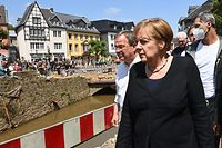 German Chancellor Angela Merkel and North Rhine-Westphalia's State Premier, Christian Democratic Union (CDU) leader and CDU's candidate for Chancellery Armin Laschet walk through the flood-ravaged spa town Bad Munstereifel, North Rhine-Westphalia state, western Germany, on July 20, 2021. - The German government on July 19, 2021 pledged to improve the country's under-fire warning systems as emergency services continued to search for victims of the worst flooding in living memory, with at least 165 people confirmed dead. (Photo by CHRISTOF STACHE / POOL / AFP)
