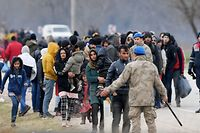 Migrants wait next Turkish soldiers as they resumed efforts to enter Europe next to the fences near Pazarkule border gate in Edirne on March 4, 2020. - Migrants and refugees clashed with Greek police on the Turkish border on March 4, 2020, as they resumed efforts to enter Europe, leaving at least one person injured according to AFP correspondents. (Photo by Ozan KOSE / AFP)
