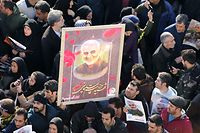 """Iranian mourners lift a picture of slain military commander Qasem Soleimani during a funeral procession in the capital Tehran on January 6, 2020, for him as well as Iraqi paramilitary chief Abu Mahdi al-Muhandis and other victims of a US attack. - Downtown Tehran was brought to a standstill as mourners flooded the Iranian capital to pay an emotional homage to Soleimani, the """"heroic"""" general who spearheaded Iran's Middle East operations as commander of the Revolutionary Guards' Quds Force and was killed in a US drone strike on January 3 near Baghdad airport. (Photo by ATTA KENARE / AFP)"""