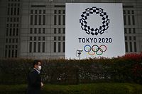 A man in a face mask walks past a display showing the Tokyo 2020 logo in Tokyo on March 23, 2020. (Photo by CHARLY TRIBALLEAU / AFP)