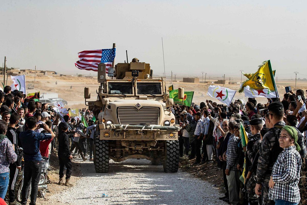 Syrische Kurden versammeln sich an der türkischen Grenze um ein US-Kampffahrzeug, um gegen die Drohungen aus der Türkei zu demonstrieren.