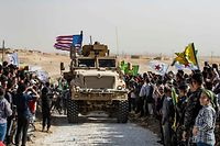 "Syrian Kurds gather around a US armoured vehicle during a demonstration against Turkish threats next to a US-led international coalition base on the outskirts of Ras al-Ain town in Syria's Hasakeh province near the Turkish border on October 6, 2019. - Ankara had reiterated on October 5 an oft-repeated threat to launch an ""air and ground"" operation in Syria against a Kurdish militia it deems a terrorist group. (Photo by Delil SOULEIMAN / AFP)"