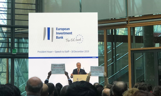 """Staff holding up signs as EIB President Werner Hoyer speaks in December 2019. The signs read: """"your staff is frustrated! What will you do please?"""""""