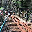 """28.06.2018, Thailand, Chiang Rai, Mae Sai:  Rettungskräfte arrangieren Schläuche, mit denen Wasser aus einer Tropfsteinhöhle, in der seit sechs Tagen eine Jugend-Fußballmannschaft eingeschlossen ist, gepumpt werden soll. Die Suche nach den zwölf Jungen und ihrem Fußballtrainer wird durch starken Regen weiter behindert. (zu dpa """"Regen erschwert Suche nach eingeschlossenen Jungen in Thailand"""" vom 28.06.2018) Foto: Hathai Techakitteranun/dpa +++ dpa-Bildfunk +++"""