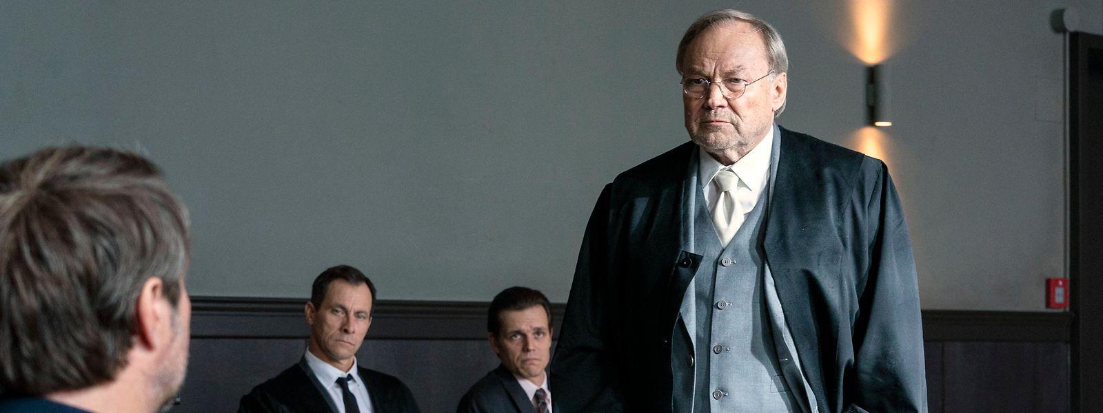 Strafverteidiger Biegler (Klaus Maria Brandauer, r.) befragt Kommissar Nadler (Bjarne Mädel, l.). Er und sein Assistent (Marc Hosemann, 2. v. l.) möchten einen Freispruch für Kelz (Franz Hartwig, 2. v. r.).