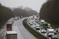 "Freight lorries are organised into stacks (L) by police on the M20 motorway which leads to the Port of Dover at Mersham in Kent, south east England on December 21, 2020, as a string of countries banned travel including accompanied freight arriving from the UK, due to the rapid spread of a more-infectious new coronavirus strain. - Britain's critical south coast port at Dover said on Sunday it was closing to all accompanied freight and passengers due to the French border restrictions ""until further notice"". (Photo by Adrian DENNIS / AFP)"