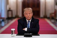 TOPSHOT - US President Donald Trump sits with his arms crossed during a roundtable discussion on the Safe Reopening of America�s Schools during the coronavirus pandemic, in the East Room of the White House on July 7, 2020, in Washington, DC. (Photo by JIM WATSON / AFP)