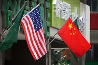 "(FILES) This file photo taken on May 14, 2019 shows the US (L) and Chinese flags displayed outside a hotel in Beijing. - Chinese and US trade representatives agreed on May 8, 2020 to ""create favourable conditions"" for the phase one trade deal signed in January, Beijing officials said, despite recent tensions over the coronavirus pandemic. (Photo by Greg Baker / AFP)"