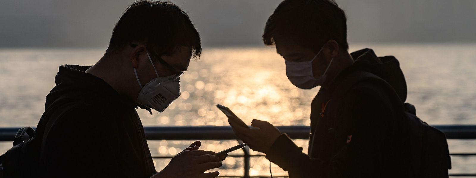 Jugendliche mit Atemschutzmasken blicken auf ihre Handys: Die Regierung in Hongkong rät, so wenig wie möglich vor die Tür zu gehen und Ansammlungen von Menschen zu meiden.