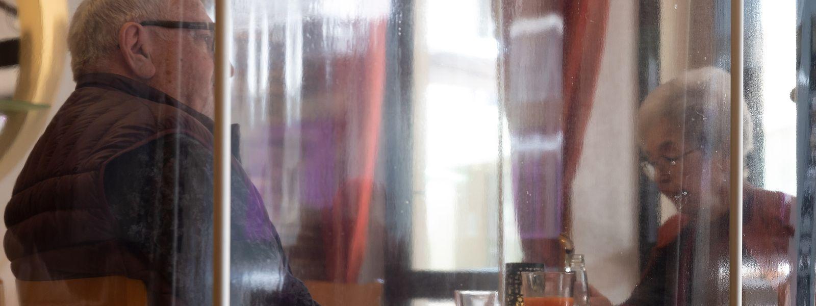 Ein Paar wartet in einem Restaurant in Echternach auf das Essen. Die Tische sind durch durchsichtige Schutzwände voneinander getrennt.