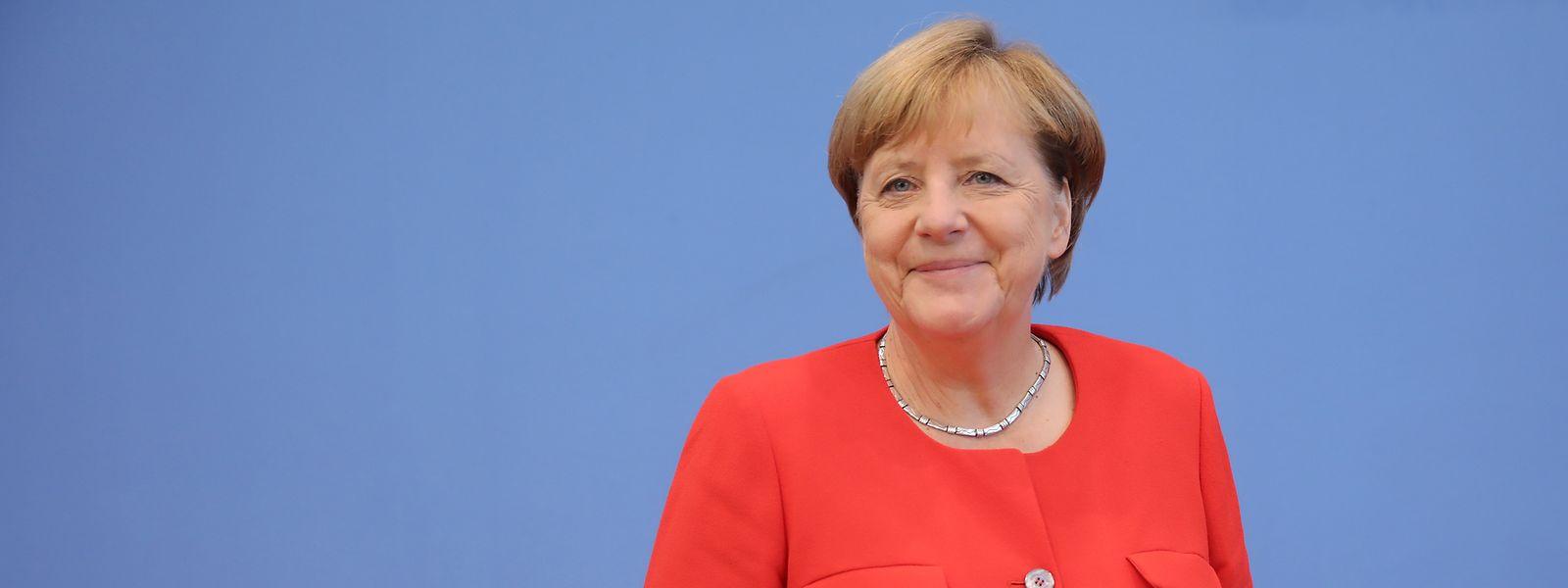 Angela Merkel im roten Blazer mit typischer Rautegeste.