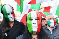 Protestors, wearing masks in the colors of Italian flag, hold flags as they take part in a protest rally against a new series of restrictions to stop a rise in Covid-19 cases, even as the government considers more stringent measures, in Rome on October 31, 2020. - The protests come as Italy reported over 31,084 new cases of the virus on octobert 30, 2020, breaking a daily record. Italy's government is eyeing a lockdown of the country's major cities, including Milan, Rome and Naples, to try to slow the alarming rise in infections, news media reported. (Photo by Alberto PIZZOLI / AFP)