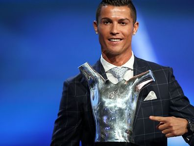 Real Madrid's Portuguese forward Cristiano Ronaldo poses with his trophy of Best Men's player in Europe at the end of the UEFA Champions League Group stage draw ceremony, on August 25, 2016 in Monaco. AFP PHOTO / VALERY HACHE