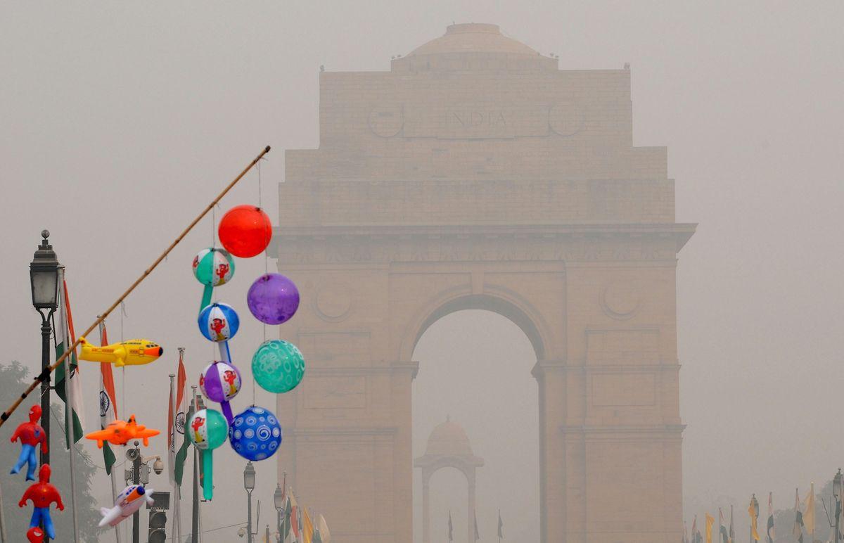 Aufblasbares Spielzeug wird, während dichter Smog über der Stadt liegt, an einer Straße verkauft.