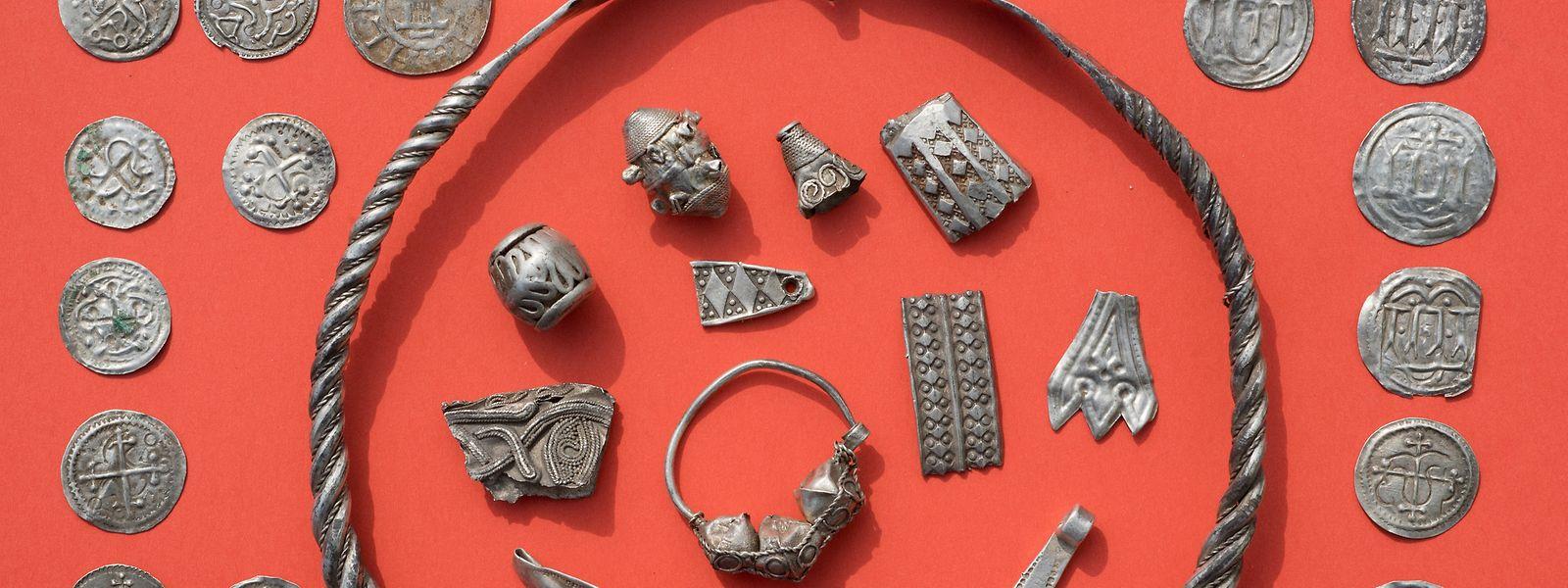 Teile des Silberschatzes von Schaprode mit gewendeltem, verschliessbarem Drahtring, Silberperlen mit Granulationsauflage, zerhacktem Silberschmuck, Thorshammeramulett und dänischen sowie ottonischen Münzen.