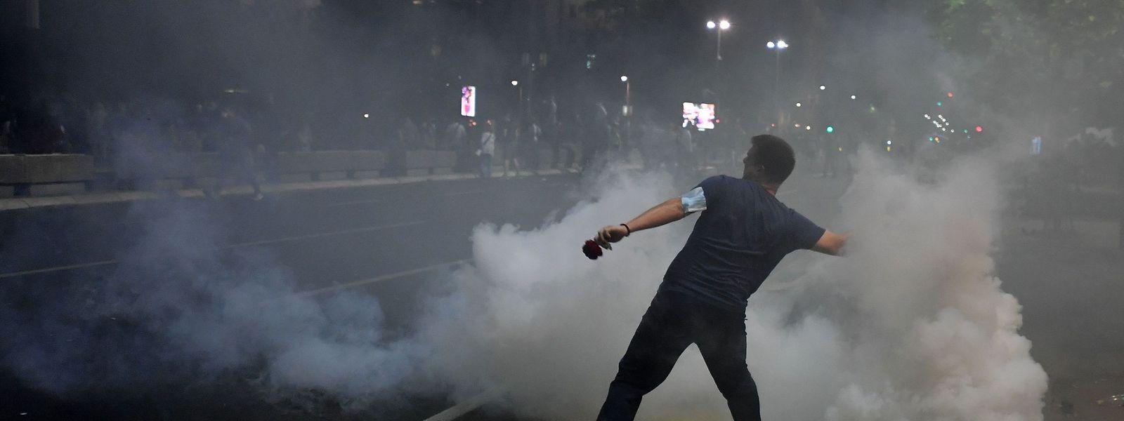 Ein Demonstrant schleudert einen Reizgas-Kanister zurück.