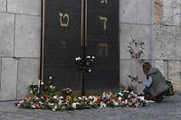 A woman lays down flowers next to the entrance of the synagogue in Munich, during a protest against anti-Semitism on October 11, 2019 two days after a deadly shooting during an attack in Halle targeting a Turkish restaurant after an attempt at the synagogue. - Jews in Germany prepared to mark the Sabbath Friday with their confidence in the community's miraculous rebirth shaken by the deadly anti-Semitic rampage in Halle on Yom Kippur. (Photo by Christof STACHE / AFP)