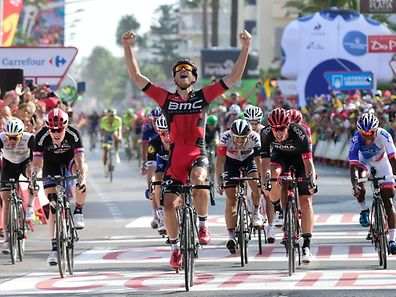 """BMC Racing Team's Luxembourgian cyclist Jean-Pierre Drucker (C) celebrates winning as he crosses the finish line during the 16th stage of the 71st edition of """"La Vuelta"""" Tour of Spain"""