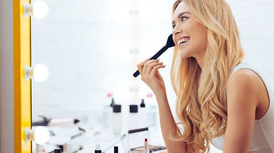 Side view of cheerful young woman plying make-up and looking at her reflection in mirror while sitting at the dressing table