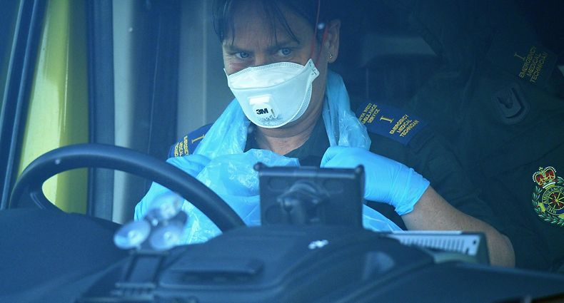 """A paramedic wearing PPE (personal protective equipment), including a face mask, gloves and an apron as a precautionary measure against COVID-19, sits in their ambulance at Aintree University Hospital in Liverpool, north west England on May 14, 2020. - Britain on Thursday said it was in discussions with Swiss pharma giant Roche to mass purchase its coronavirus antibody test after scientists claimed it was """"100 percent"""" accurate. """"This test developed by Roche appears to be extremely reliable, it's got the green light from testers,"""" health minister Edward Argar told the BBC on Thursday. (Photo by Oli SCARFF / AFP)"""