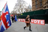 """A pedestrian walks pas a placard reading """"People's Vote"""" as Brexit activits demonstrate outside of the Houses of Parliament in central London on January 21, 2019, whilst Britain's Prime Minister Theresa May makes a statement to the House of Commons on changes to her Brexit withdrawal agreement. - British Prime Minister Theresa May unveils her Brexit """"Plan B"""" to parliament on Monday after MPs shredded her EU divorce deal, deepening the political gridlock 10 weeks from departure day. (Photo by Tolga AKMEN / AFP)"""