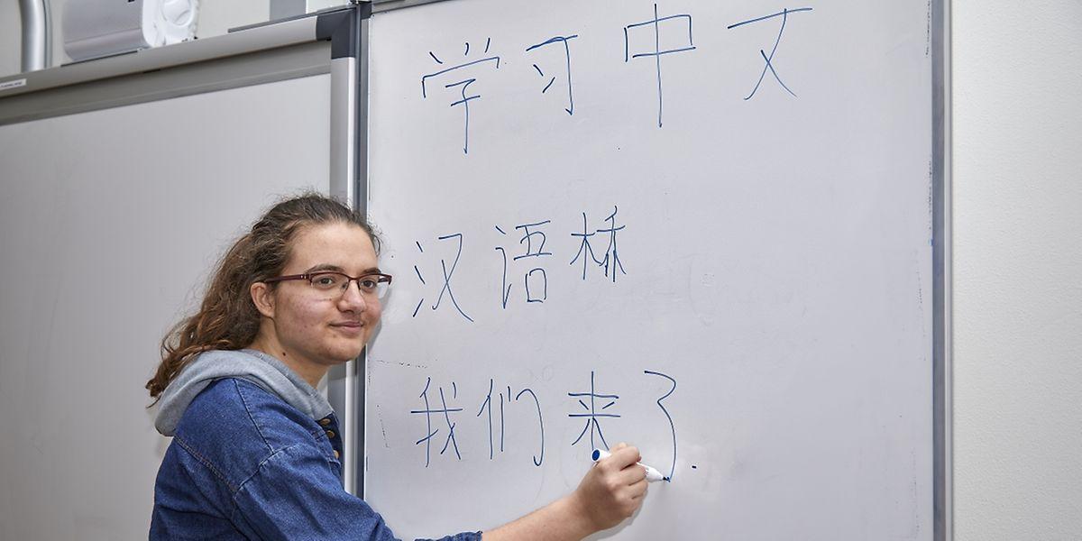 """Die chinesischen Schriftzeichen stellen für Flora Varhegyi keine besondere Herausforderung dar. So schreibt sie auch in Mandarin das Motto des Sprachwettbewerbs an die Tafel: """"Chinesisch lernen"""" (oben); """"Chinese Bridge"""" (Mitte); """"Wir kommen (unten)."""""""