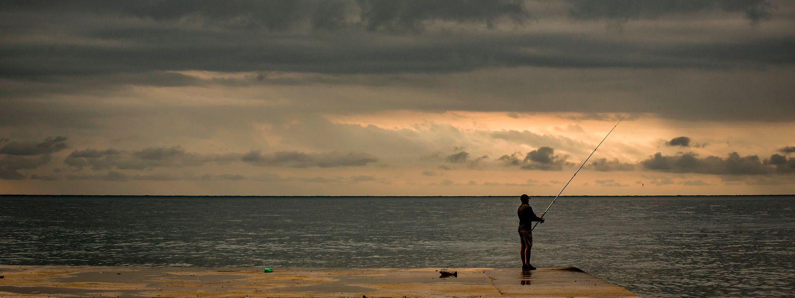 Barcelona: Die Sonne geht nach einer stürmischen Nacht am Horizont auf, während ein Mann seine Angel in der Mole von La Barceloneta auswirft.