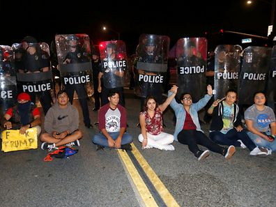 Demonstrators sit in front of a line of police in riot gear outside Republican U.S. presidential candidate Donald Trump's campaign rally in Costa Mesa, California April 28, 2016.     REUTERS/Mike Blake