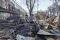 TOPSHOT - Migrants sit inside the burnt Moria Camp on the Greek island of Lesbos on September 9, 2020, after a major fire. - Thousands of asylum seekers on the Greek island of Lesbos fled for their lives early September 9, as a huge fire ripped through the camp of Moria, the country's largest and most notorious migrant facility. Over 12,000 men, women and children ran in panic out of containers and tents and into adjoining olive groves and fields as the fire destroyed most of the overcrowded, squalid camp. The blaze started just hours after the migration ministry said that 35 people had tested positive at the camp. (Photo by Anthi PAZIANOU / AFP)