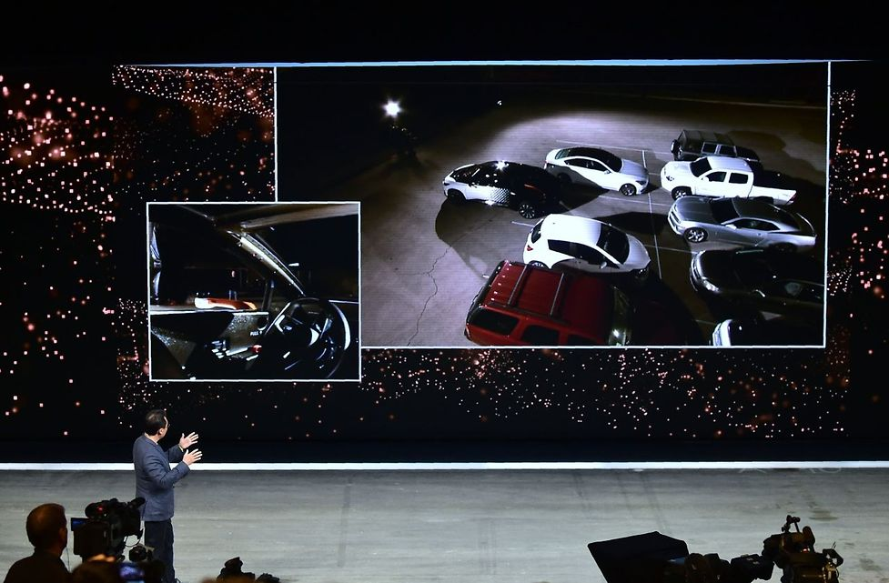 Faraday Future's Hong Bae, Director if ADAS + Self Driving gestures while giving the audience a live display on the screen of a self-driving and parking FF91 electric vehicle