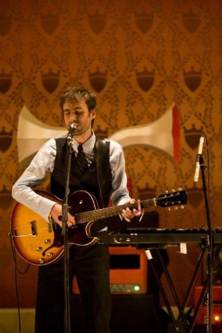 Mann mit Gitarre und professioneller Zwitscherer
