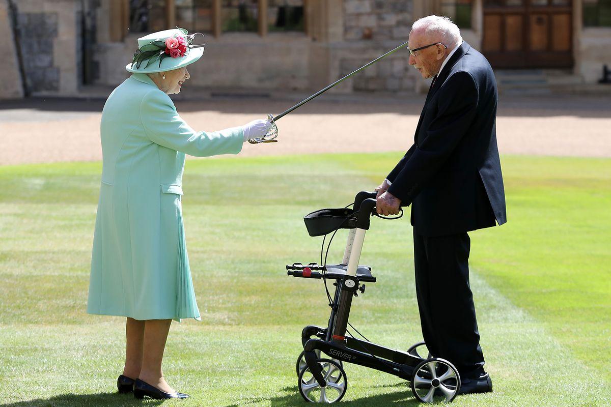 Königin Elizabeth II. (l) schlägt Tom Moore (r), Weltkriegsveteran und Rekord-Spendensammler, während einer Zeremonie im Freien auf Schloss Windsor zum Ritter.