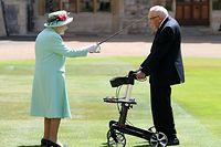 17.07.2020, Großbritannien, Windsor: Königin Elizabeth II. (l) schlägt Tom Moore (r), Weltkriegsveteran und Rekord-Spendensammler, während einer Zeremonie im Freien auf Schloss Windsor zum Ritter. Moore hatte mit einem Spendenlauf am Rollator in der Corona-Krise knapp 33 Millionen Pfund (etwa 36 Millionen Euro) gesammelt und es damit ins Guinness-Buch der Rekorde geschafft. Das Geld ging an den chronisch unterfinanzierten staatlichen Gesundheitsdienst NHS. Foto: Chris Jackson/PA Wire/dpa +++ dpa-Bildfunk +++