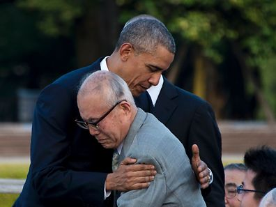 US President Barack Obama hugs Shigeaki Mori (front), a survivor of the 1945 atomic bombing of Hiroshima, during a visit to the Hiroshima Peace Memorial Park on May 27, 2016. Obama on May 27 paid moving tribute to victims of the world's first nuclear attack.   / AFP PHOTO / JIM WATSON