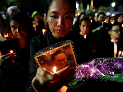 Mourners hold candles as they gather outside of the Grand Palace to sing for a recording of the royal anthem in honour of Thailand's late King Bhumibol Adulyadej in Bangkok, Thailand, October 22, 2016. REUTERS/Jorge Silva
