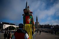 A pilgrim holds a statue of Our Lady Fatima along with a Portuguese flag during a ceremony marking the last pilgrimage of the year at the Fatima shrine in central Portugal held under strict social distancing rules because of the coronavirus pandemic on October 13, 2020. (Photo by PATRICIA DE MELO MOREIRA / AFP)