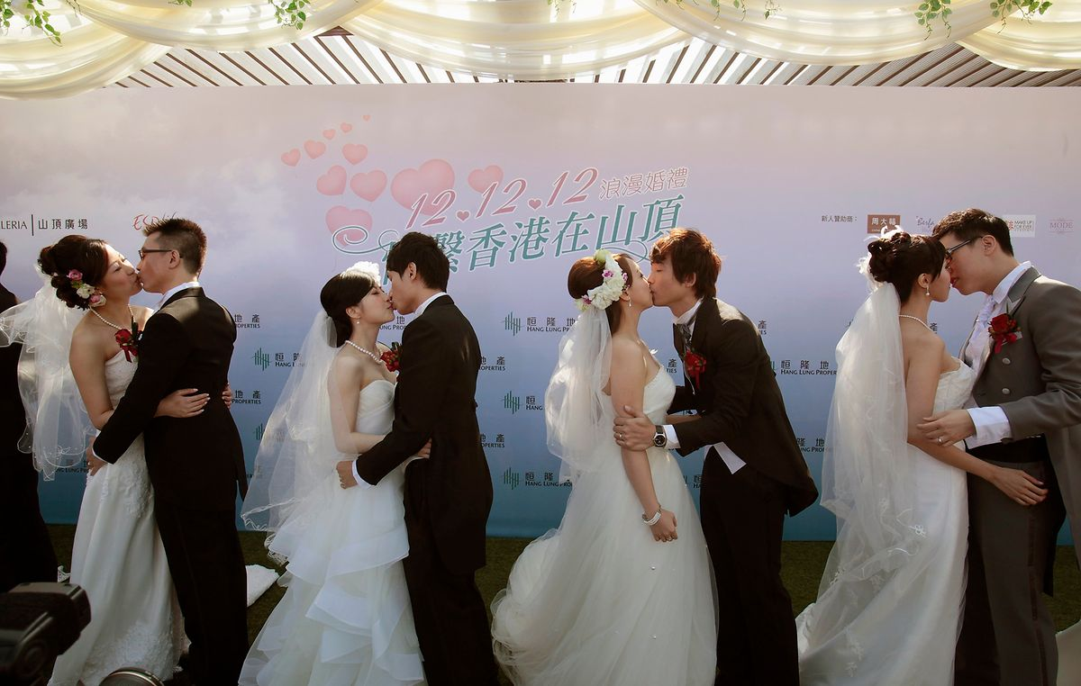 Four of 12 couples kiss after exchanging rings during a wedding ceremony at the Peak in Hong Kong, an event to celebrate weddings on the date of December 12, 2012.  REUTERS/Bobby Yip (CHINA - Tags: SOCIETY)