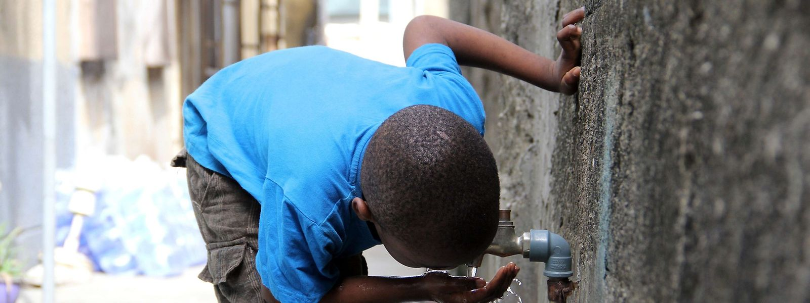 A boy drinks from a public tap in Lagos on March 19, 2015. AFP PHOTO/AREWA EMMANUEL