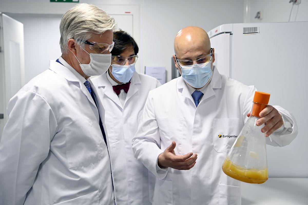 Philippe (l), König von Belgien, und Elio Di Rupo (hinten M), Ministerpräsident von Wallonien, hören in einem Labor einem Mitarbeiter von Eurogentec zu.