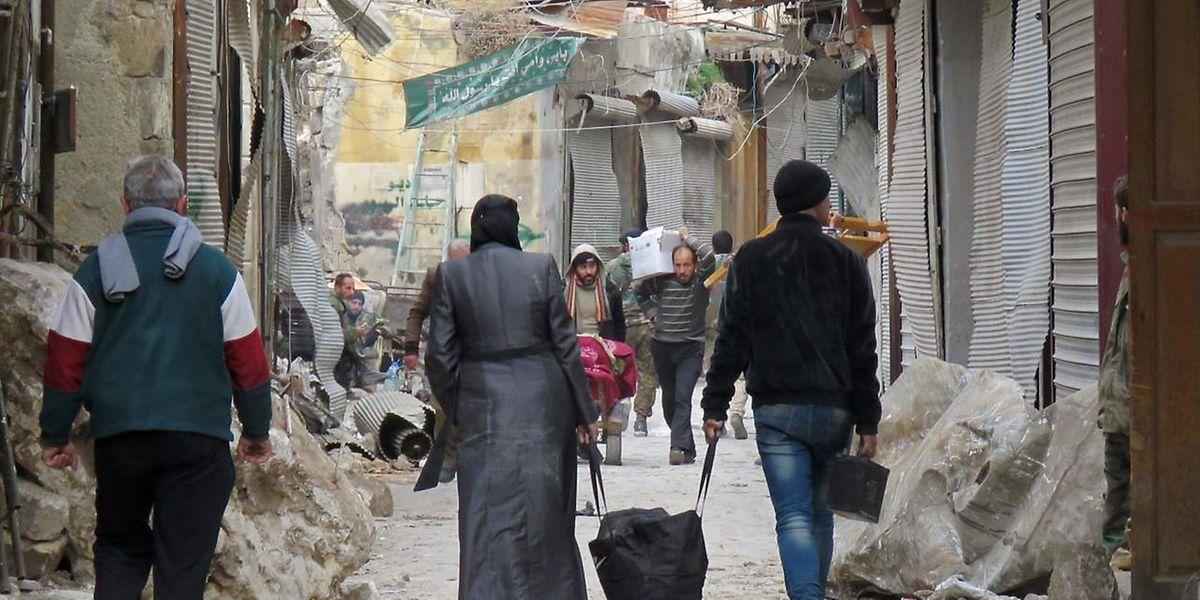 Des résidents d'Alep parcourent le vieux marché de leur ville, détruit, en décembre 2016.