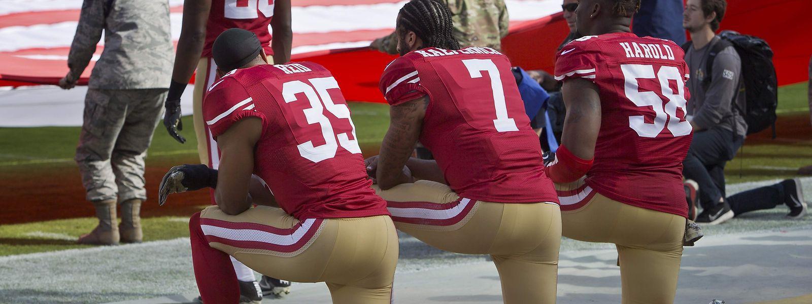 Colin Kaepernick (7), Eric Reid (35), und Eli Harold (58) knien während der Hymne.