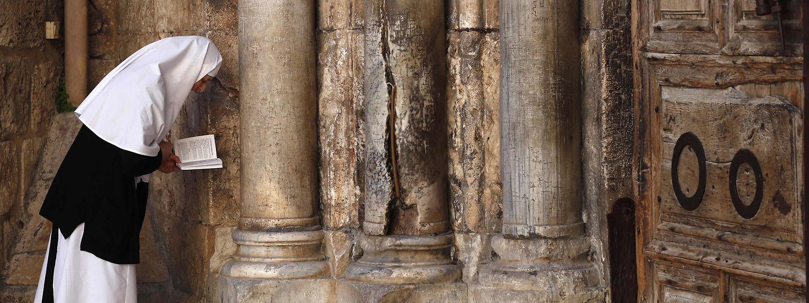 Vor der verschlossenen Tür der Jerusalemer Grabeskirche betet eine Nonne.