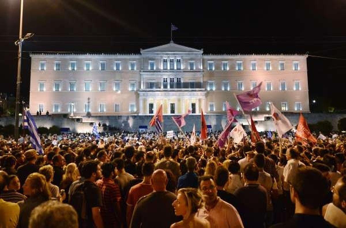 """Sur la place Syntagma, des milliers de personnes se sont rassemblées pour manifester leur joie, malgré les incertitudes. Certains chantaient, dansaient, agitaient des drapeaux et scandaient """"Oxi"""" (Non en grec), leurs visages rayonnants."""